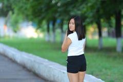 走在公园的女孩是走的步态 免版税库存图片