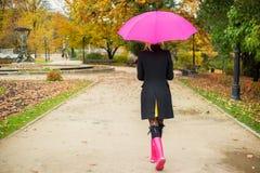 走在公园的妇女在秋天 免版税库存图片