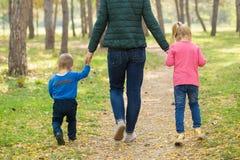 走在公园的妈妈、儿子和女儿在日落 图库摄影