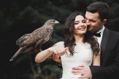 走在公园的愉快的新婚佳偶时髦的夫妇在他们的与花束的婚礼之日 免版税库存图片
