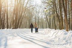 走在公园的愉快的年轻家庭在冬天 父母通过雪怀有婴儿推车的婴儿 免版税图库摄影