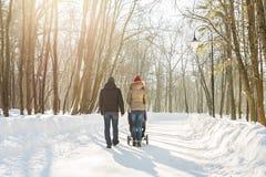走在公园的愉快的年轻家庭在冬天 父母通过雪怀有婴儿推车的婴儿 免版税库存照片