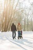 走在公园的愉快的年轻家庭在冬天 父母通过雪怀有婴儿推车的婴儿 图库摄影