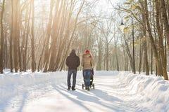 走在公园的愉快的年轻家庭在冬天 父母通过雪怀有婴儿推车的婴儿 库存照片