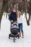 走在公园的愉快的年轻家庭在冬天 免版税库存图片