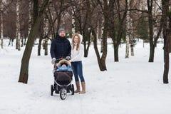 走在公园的愉快的年轻家庭在冬天 库存图片