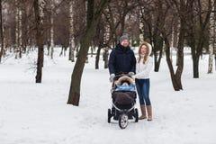 走在公园的愉快的年轻家庭在冬天 免版税图库摄影