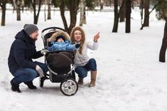 走在公园的愉快的年轻家庭在冬天 免版税库存照片