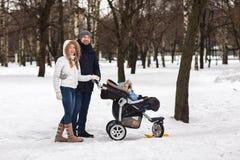 走在公园的愉快的年轻家庭在冬天 图库摄影