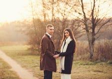 走在公园的浪漫夫妇在日落 免版税库存图片