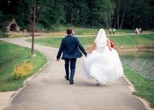 走在公园的爱恋的夫妇在他们的婚礼之日 免版税库存照片