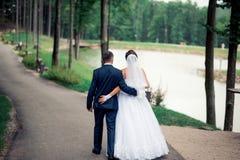 走在公园的爱恋的夫妇在他们的婚礼之日 免版税库存图片