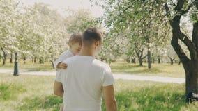 走在公园的父亲和儿子 年轻父亲和小儿子获得乐趣户外 影视素材