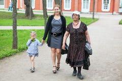 走在公园的祖母、母亲和年轻女儿 库存照片