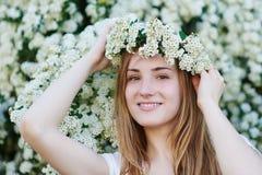 走在公园的美丽的妇女在白色开花的树附近 免版税库存照片