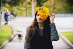 走在公园的美丽的愉快的女孩秋天室外画象  库存图片