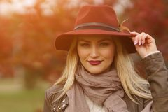 走在公园的美丽的白肤金发的女孩 免版税库存图片