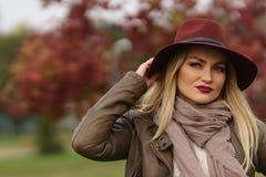走在公园的美丽的白肤金发的女孩 图库摄影
