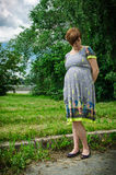走在公园的年轻人孕妇在河旁边 免版税库存图片