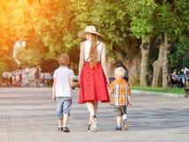 走在公园,晴天的妈咪和两个儿子 回到视图 库存图片