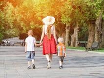 走在公园,晴天的妈咪和两个儿子 回到视图 免版税库存照片