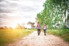 走在农村路的年轻行家夫妇享用与自然, 库存照片