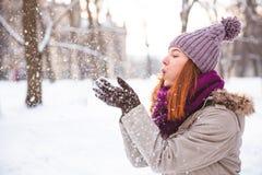 走在冬天公园的愉快的红头发人妇女和享用雪 免版税图库摄影