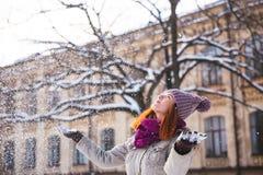 走在冬天公园的愉快的红头发人妇女和享用雪 库存照片