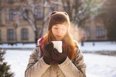 走在冬天公园的愉快的红头发人妇女和享用雪 免版税库存图片