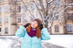 走在冬天公园的愉快的红头发人妇女和享用雪 库存图片