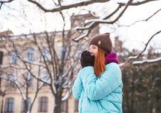 走在冬天公园的愉快的红头发人妇女和享用雪 免版税库存照片