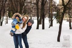 走在冬天公园的愉快的年轻家庭 库存图片
