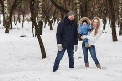 走在冬天公园的愉快的年轻家庭 库存照片