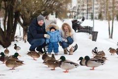 走在冬天公园的愉快的年轻家庭 免版税库存照片