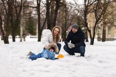 走在冬天公园的愉快的年轻家庭 免版税图库摄影