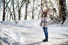 走在冬天森林里的妇女和获得乐趣 库存照片