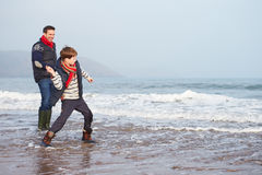 走在冬天海滩和投掷的石头的父亲和儿子 免版税库存照片
