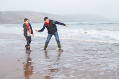 走在冬天海滩和投掷的石头的父亲和儿子 免版税库存图片