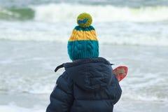 走在冬天海滩的男孩 免版税库存照片