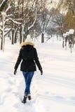 走在冬天雪公园的女孩 免版税库存图片