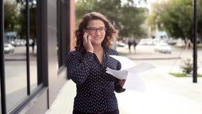 走在办公室旁边的女商人谈话在庆祝她的成功和在天空中的电话投掷文件 影视素材