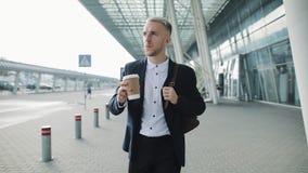走在办公楼和饮用的咖啡附近的年轻商人 帅哥享用早晨咖啡对进行缓慢行动 影视素材