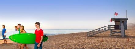 走在加利福尼亚的冲浪者青少年的男孩女孩靠岸 免版税库存图片