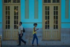 走在加勒比五颜六色的共产主义殖民地镇,哈瓦那,古巴,美国街道的现代古巴年轻人  库存图片