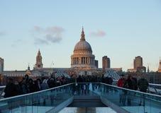 走在千年桥梁在黄昏,伦敦,英国的人们 库存图片