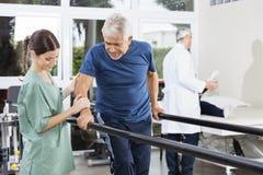 走在双杠之间的生理治疗师支持的患者 库存照片
