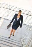 走在台阶的年轻女实业家 免版税库存图片