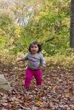 走在叶子的女婴秋天 库存图片