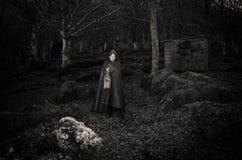 走在哥特式森林里的黑暗的妇女 库存图片