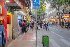 走在商代硖石jiu走的街道的不知道中国人在广州市 商代xia jiu走的街道 库存照片